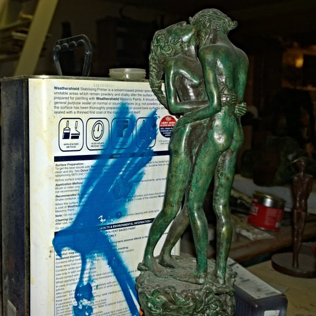A bronze of two lovers next to an old oil can next with a spray painted bird