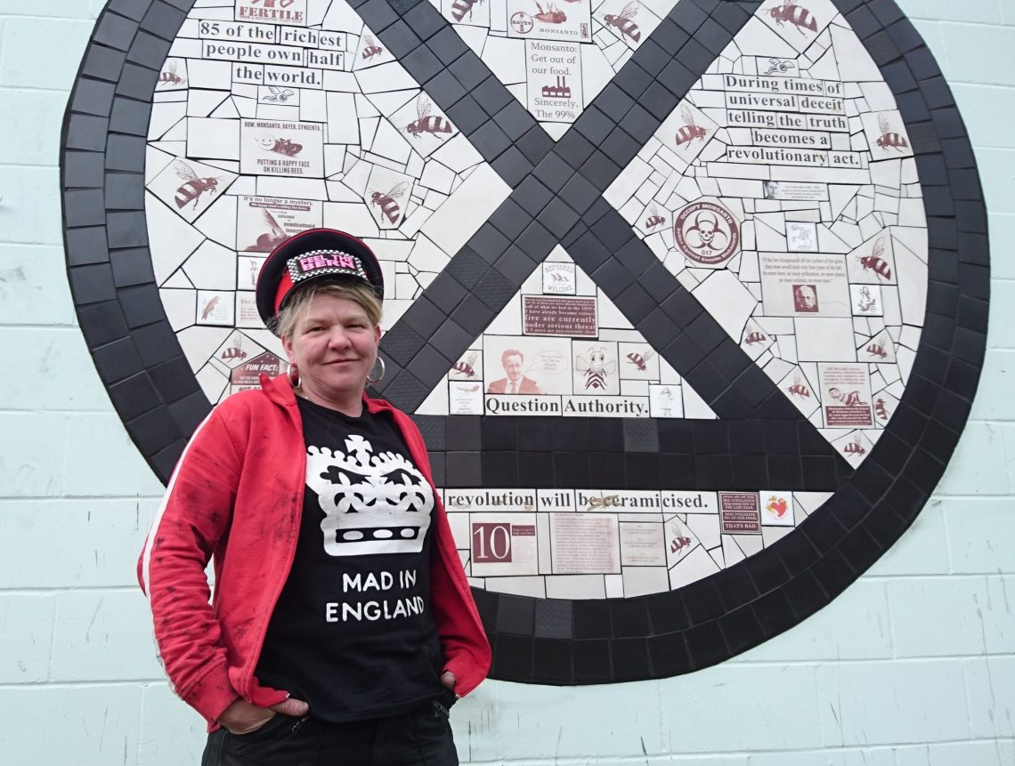 Carrie Reichardt next to her Extinction Rebellion Mosaic in Tower Hamlets