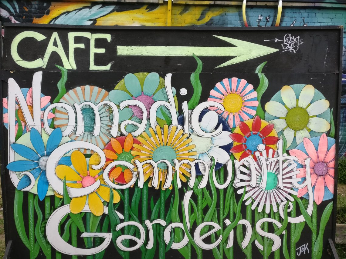 A sign for the Nomadic Community Garden on Brick Lane