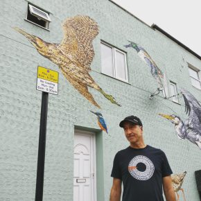 Street artist ATM standing next to his bird mural on Coppermill Lane