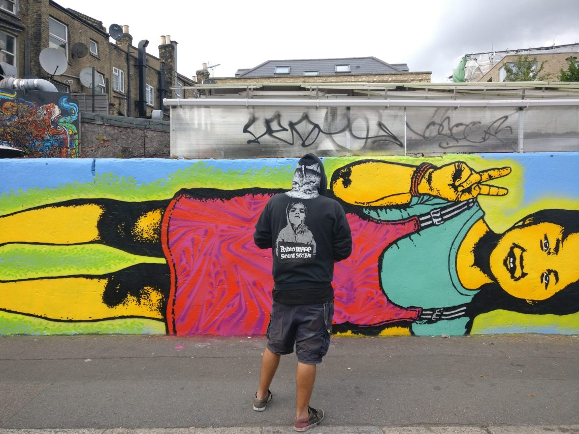 Street artist Stinkfish stands next to a mural he painted in London