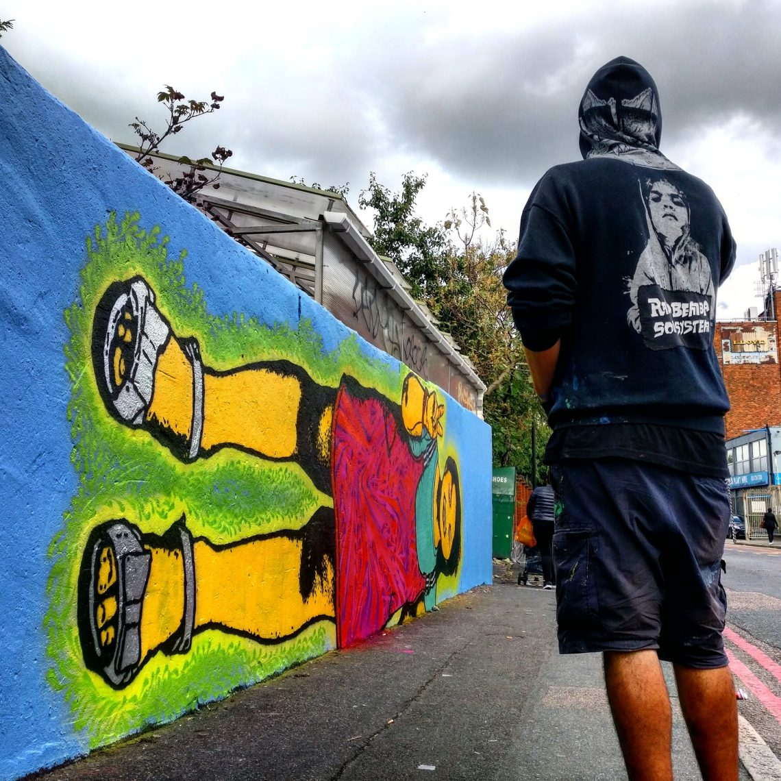 Stinkfish stands next to his street art work in Dalston, London