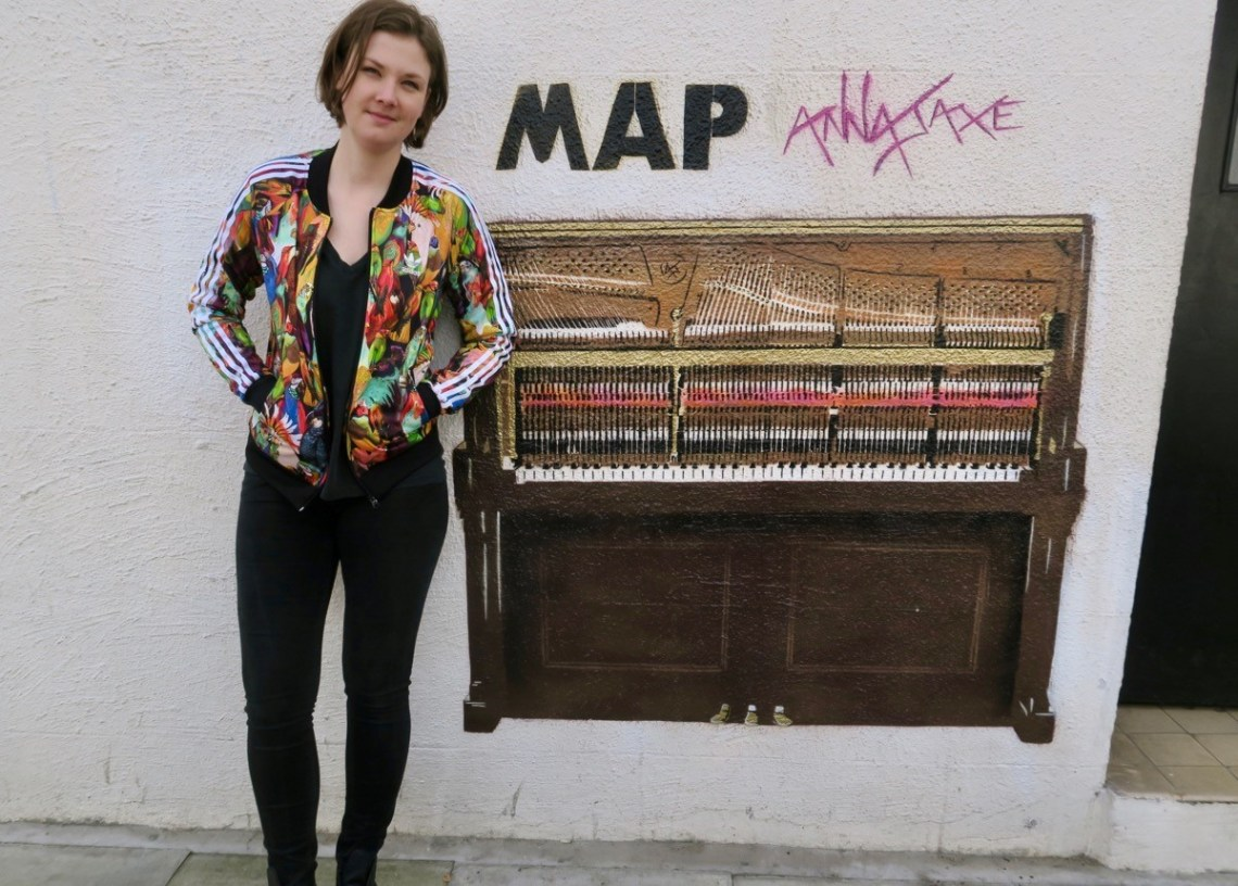 Anna Jaxe standing next to her stencil of a piano at the MAP Studio