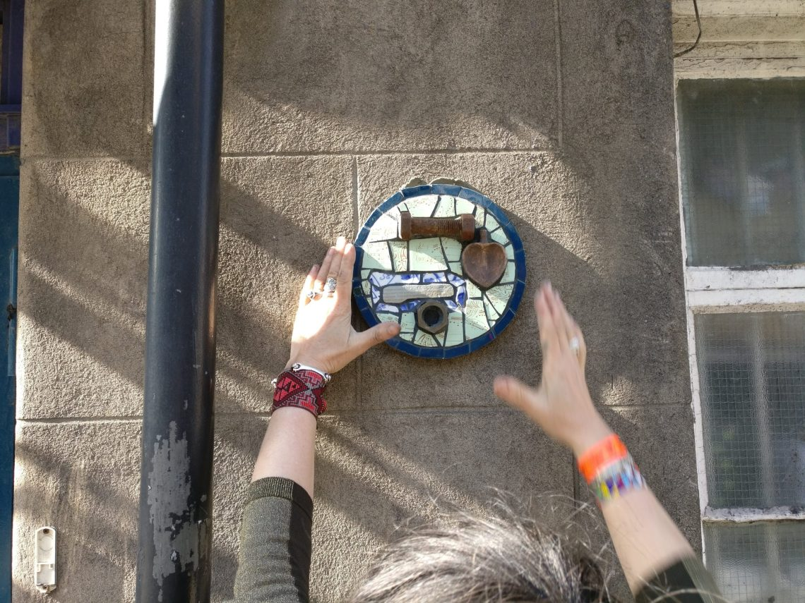Karen Francesca placing one of her micro mosaics on a wall in Aberdeen