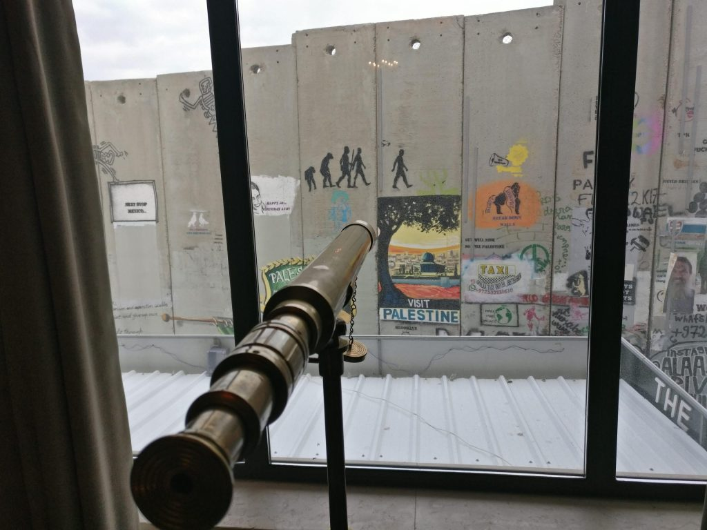 One of the views from one of the hotel rooms in Bethlehem's Walled Off Hotel. It shows a telescope looking out onto the West Bank Barrier