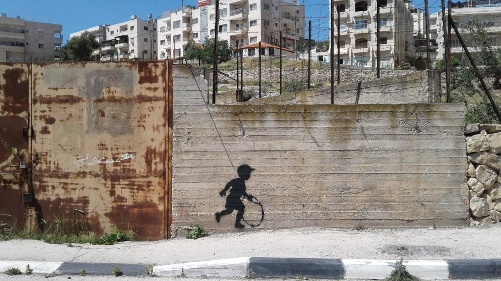 A boy plays with a barbed wire hoop by the artist cakes stencils