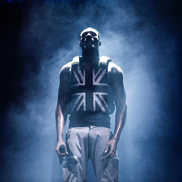 Stormzy performing at Glastonbury in the stab proof vest by Banksy