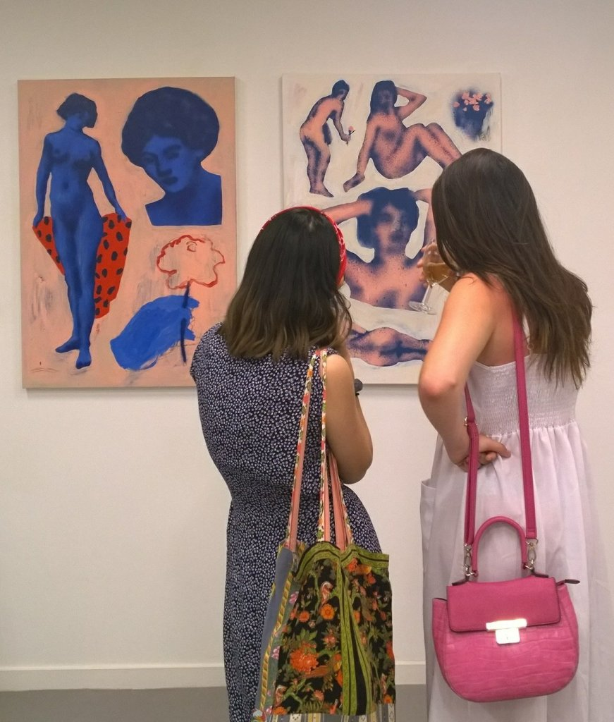 Two visitors look at work by Broken Fingaz at the Alchemy Exhibition at the Saatchi Gallery