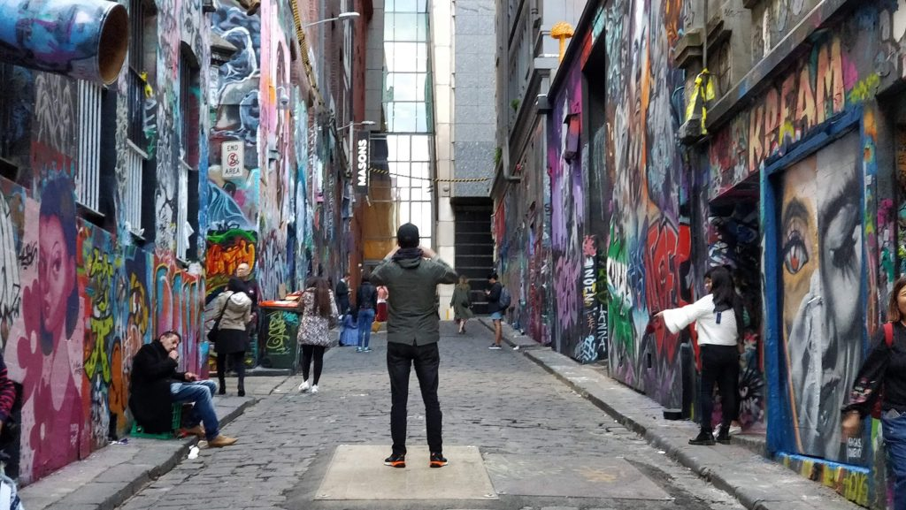 A man takes photographs on Hosier Lane in Melbourne