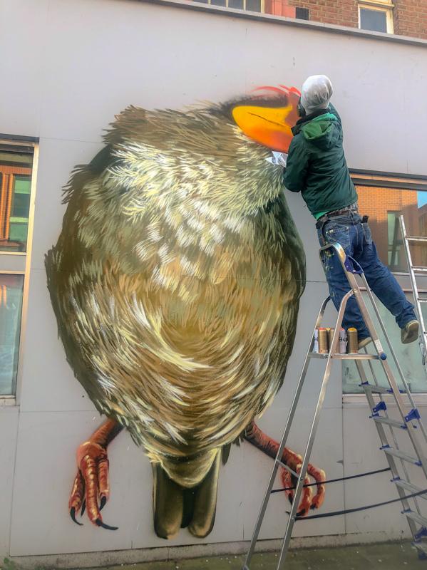 Louis Masai painting his Sparrow street art in Wimbledon