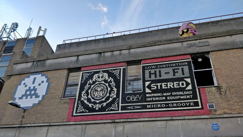 Murals from Invader and Shepard Fairey overlooking the Truman Brewery on Brick Lane