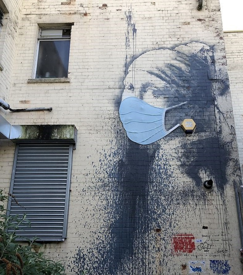 Banksy's Girl with a Pierced Eardrum now complete with a face mask. Coronavirus street art