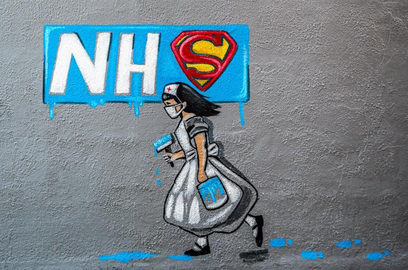 Coronavirus street art from Rachel List in Pontefract, England. It shows a nurse painting the NHS logo