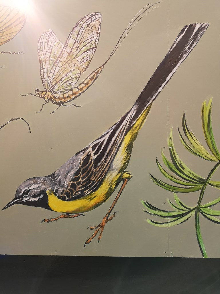 A Caddis Fly and a Grey Wagtail part of the New River mural by ATM at Palmers Green station