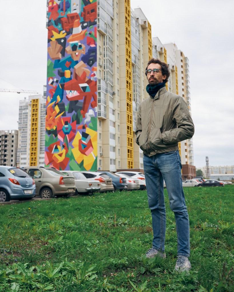 Artist Vitaly Tsarenkov by his 'Love for Nature' mural in Chelyabinsk