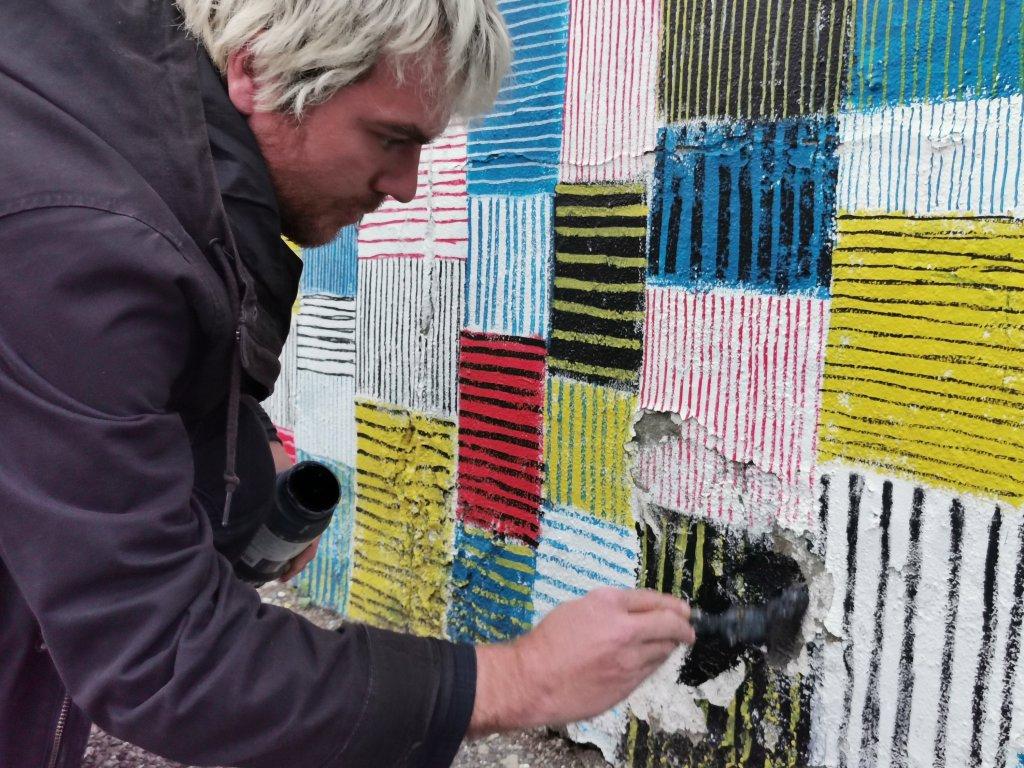 ALO the artist repairing a piece of street art