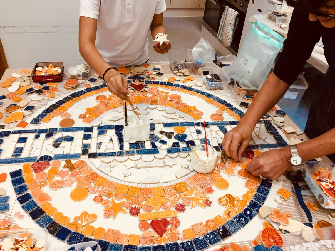 The mosaic roundel at highams park being created.