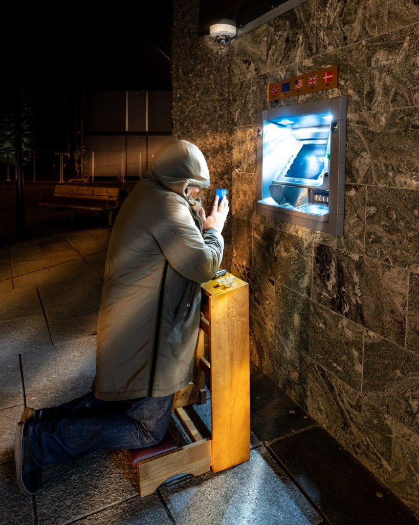 Man prays on a wooden prayer bench in front of a cash machine. The light streams down on the man as if it were a religious moment
