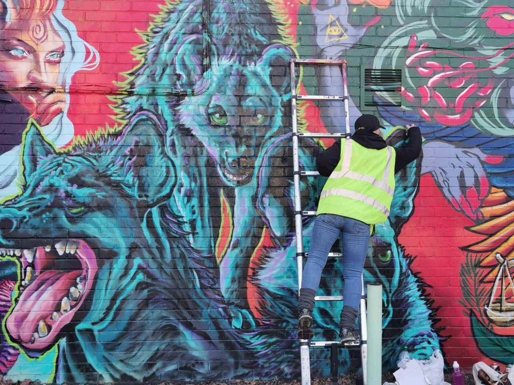 Layla Cope painting a mural with the WOM Collective in Brixton