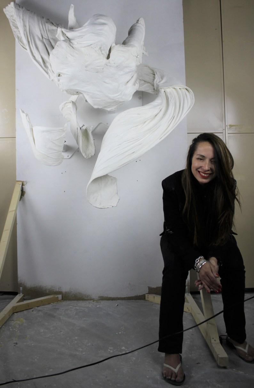Jasmin Pradissitto sitting next to her sculpture breathe