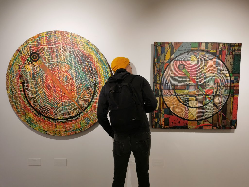 A man looks at art in the Hoxton Gallery showing the thirteenth stroke exhibition