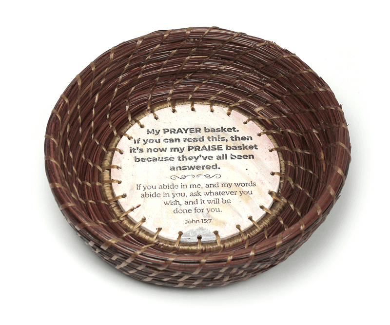 Image of a hand-woven pine straw basket by Patti Jones featuring a hand-made base with writing by Stephen Rountree and a Scripture from John 15:7