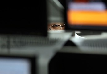 Tokyo, Japan: An employee at a foreign exchange trading company looks at monitors