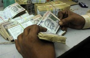 An employee counts currency notes at a cash counter inside a bank in Agartala