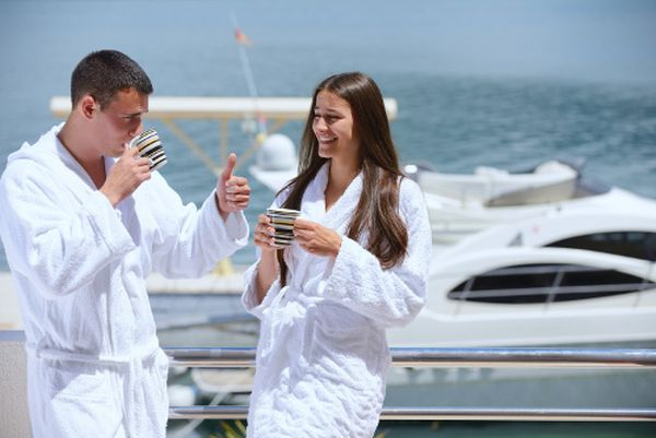 Romantic young couple spending time together and relaxing on yacht