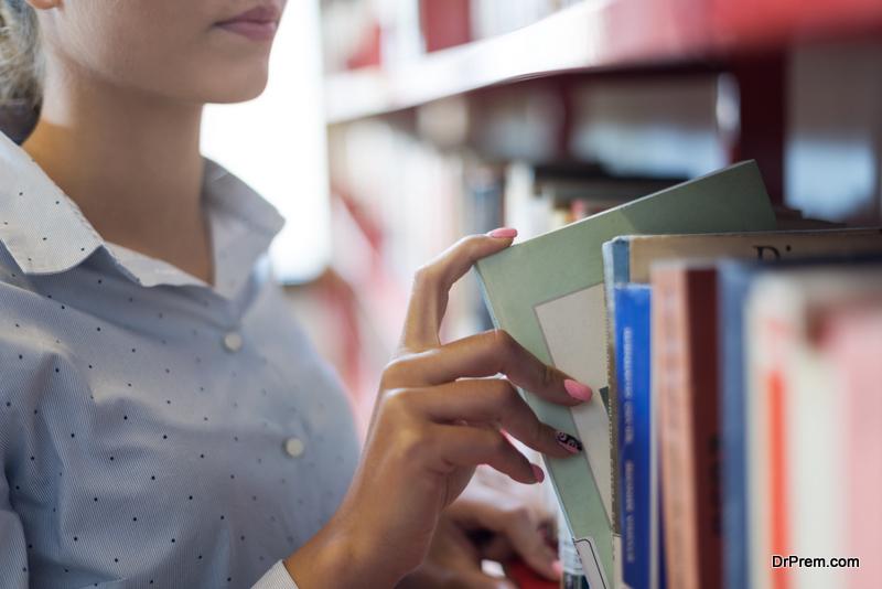 student-choosing-a-book-from-shelf