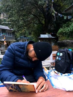 Niranjan writing his travel journal.