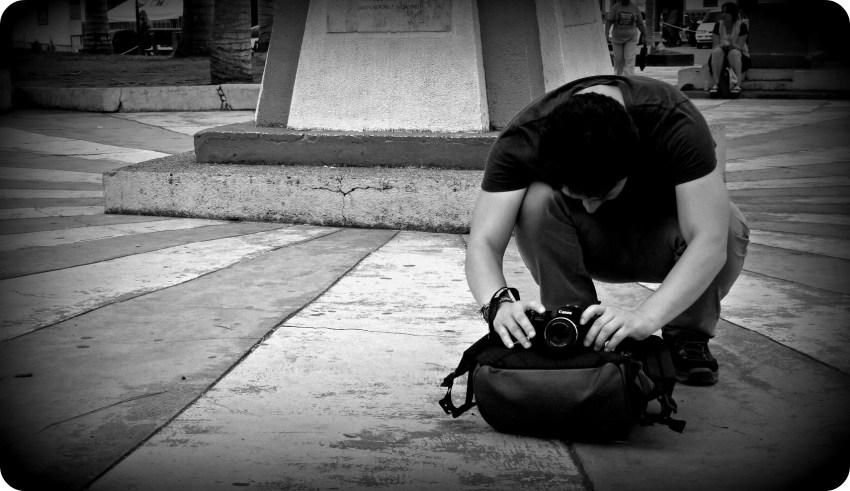 Photo en noir et blanc de Charles positionnant son appareil photo sur notre sac à dos afin de prendre la photo de goupe