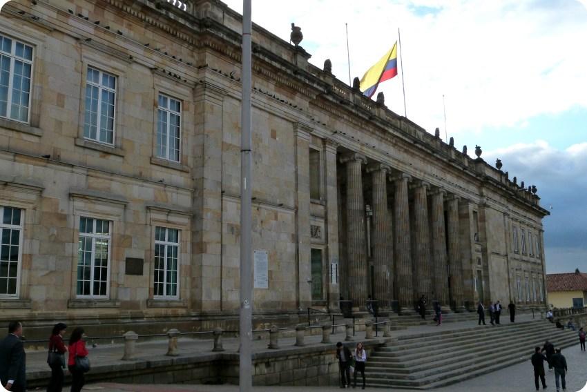 Bâtiment à colonnes avec le drapeau de la Colombie sur la place Bolívar de Bogotá