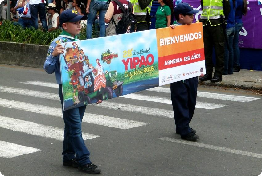 Niños llevando la pancarta en el desfile del Yipao en Armenia