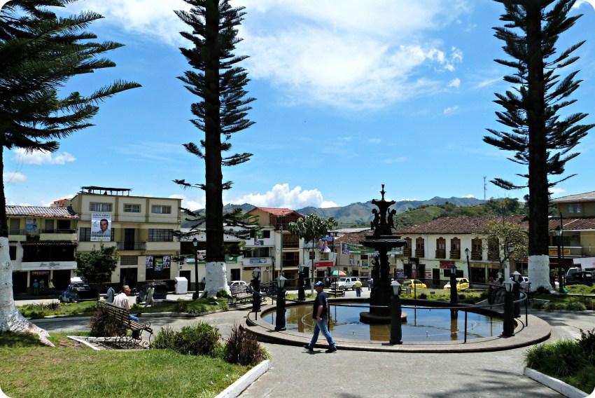 Plaza principal de Aguadas con una fuente y grandes árboles