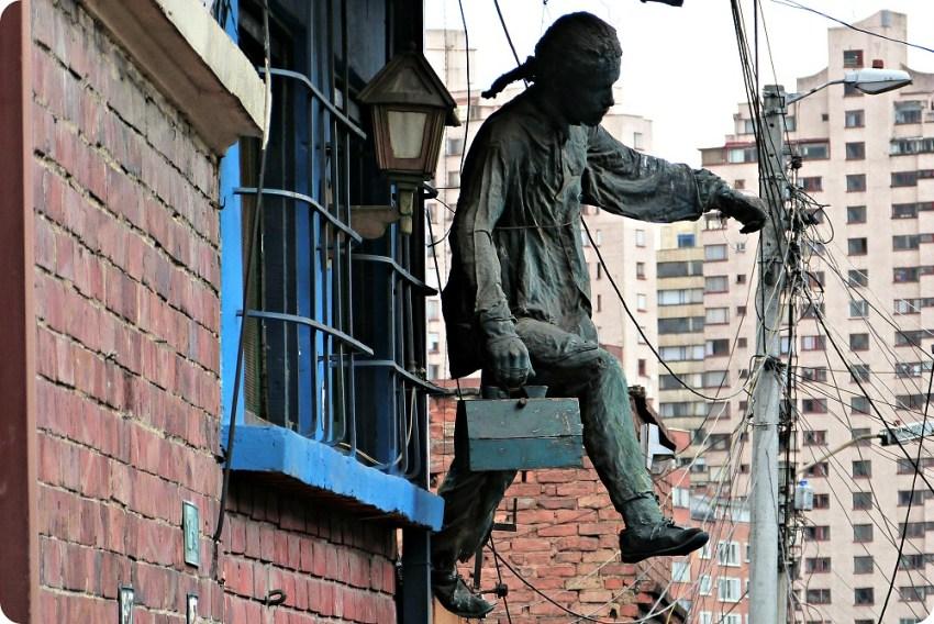 Sculpture d'un homme portant une malette accroché à une fenêtre du quartier de la Candelaria à Bogotá