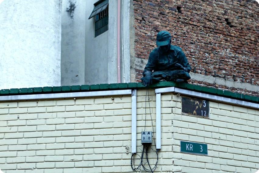 Escultura de un hombre en lo alto de un edifio con los alambres de una caja electríca en el barrio de la Candelaria en Bogotá