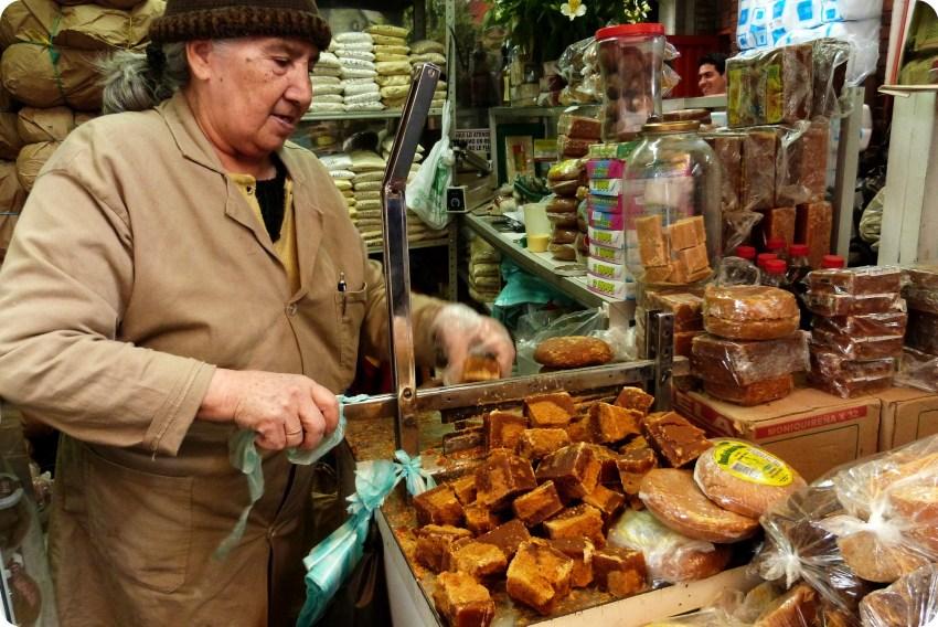 Femme âgée coupant de la panela au marché de Bogotá