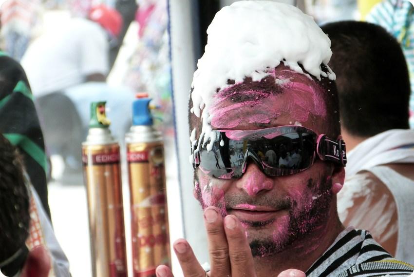 hombre con gafas y espuma sobre la cabeza en el carnaval de Pasto
