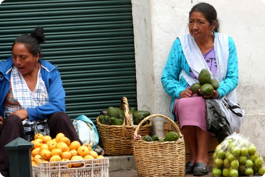 mujer vendiendo aguacates en una calle de Quito