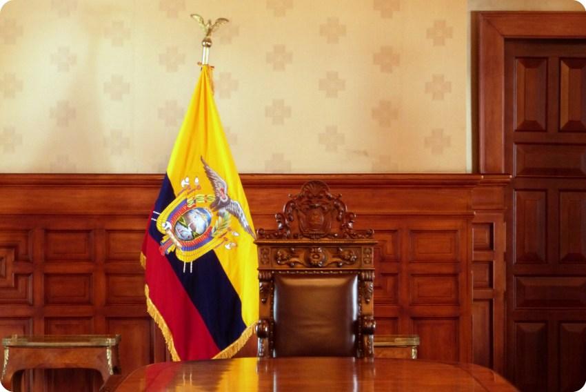 silla en una gran mesa y la bandera de Ecuador en el Palacio Presidencial de Quito