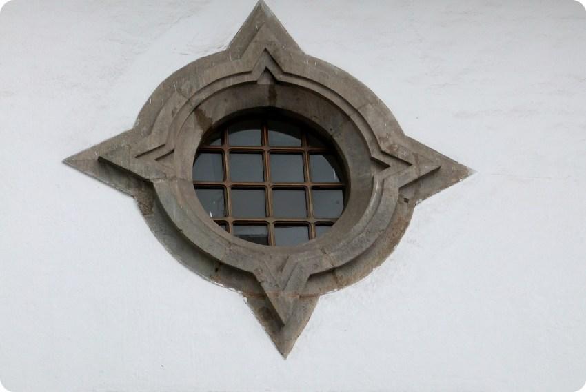 fenêtre ronde sur un bâtiment blanc du centre ville de Quito