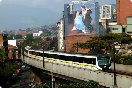 metro y pintura de Botero en un muro vistos desde el Palacio de la Cultura de Medellín