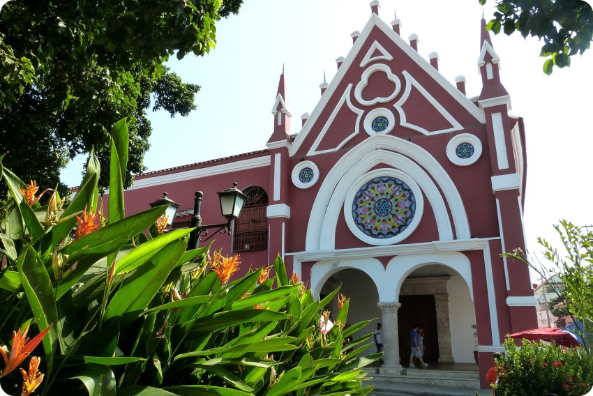 bâtiment rose rouge ressemblant à une église avec un superbe vitrail au dessus des voûtes de l'entrée