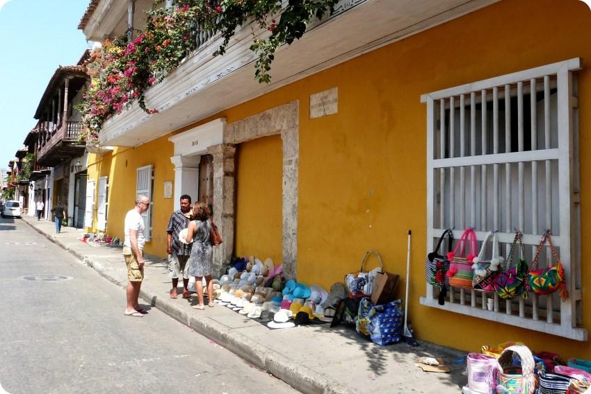 vente de souvenirs (chapeaux, sacs) dans une rue colorée de Carthagène, un couple discute avec un vendeur
