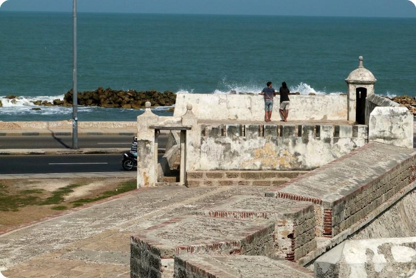 2 hommes de dos accoudés sur les murailles de Carthagène discutant et regardant la mer des Caraïbes en arrière plan