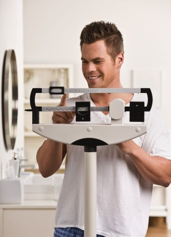 bigstock_Attractive_male_weighing_himse_27201419.jpg