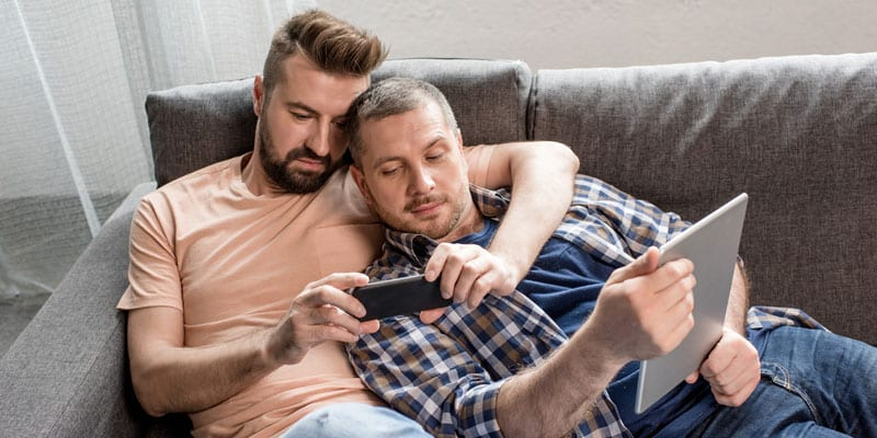 A gay couple searches the internet for a new home
