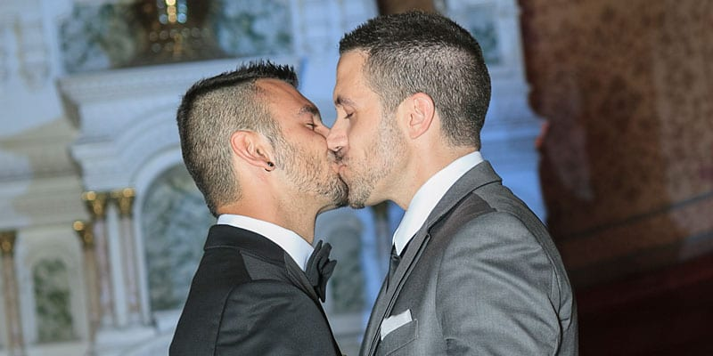A gay couple kisses during their wedding