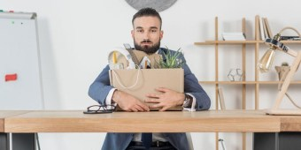 A fired employee sits at his desk